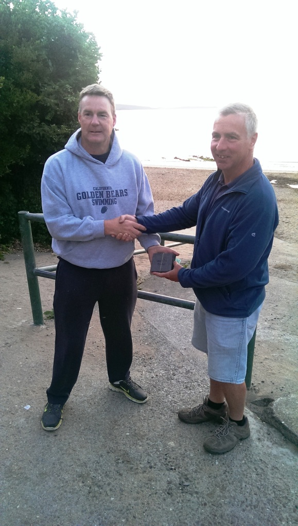 Rob Bohane presents Jim Shalloo with his prize from the Beginish swim - in Myrtleville, of course.  Where else?